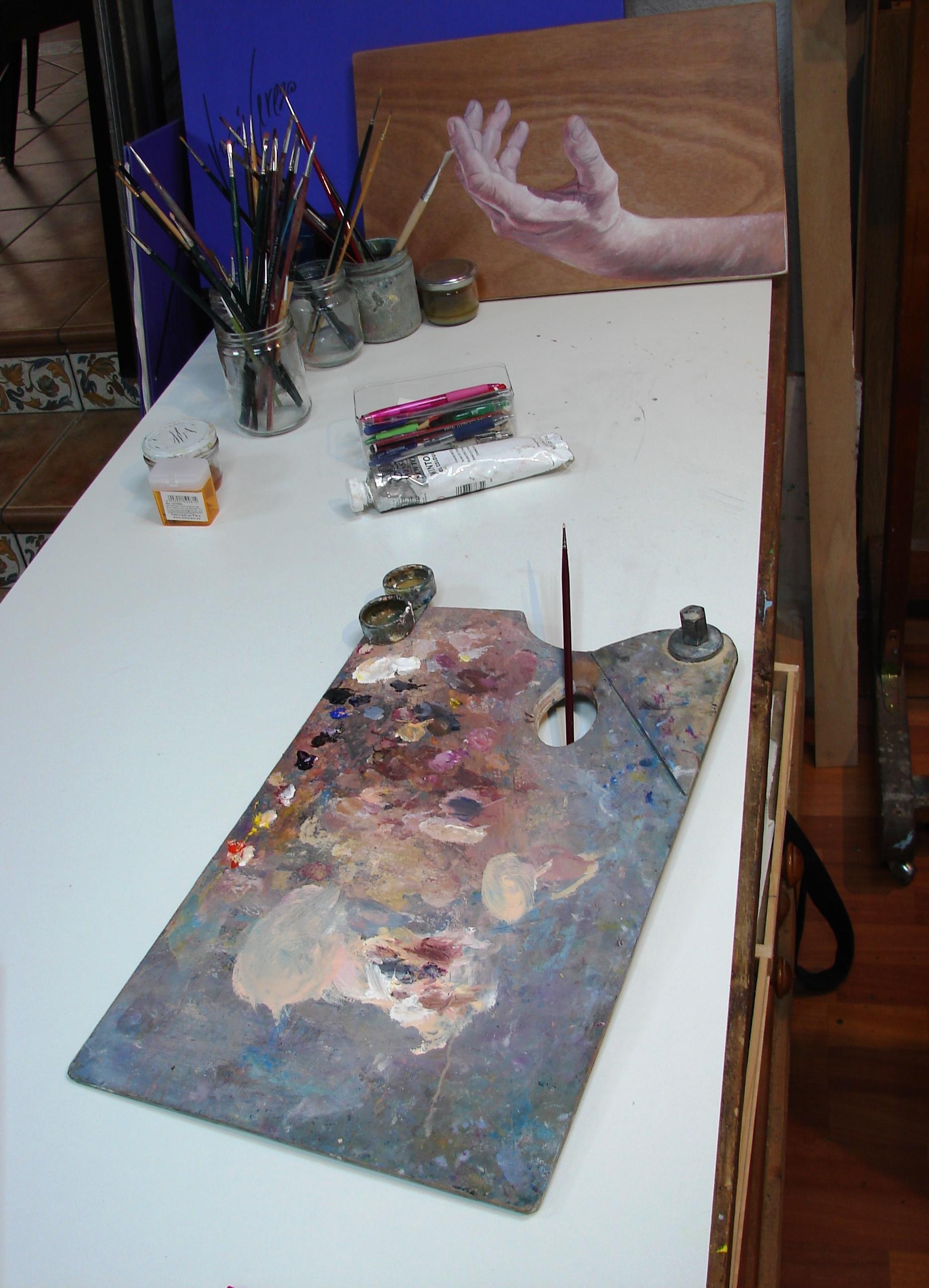 Mesa de trabajo con paleta de colores y un estudio de mano sobre madera al fondo