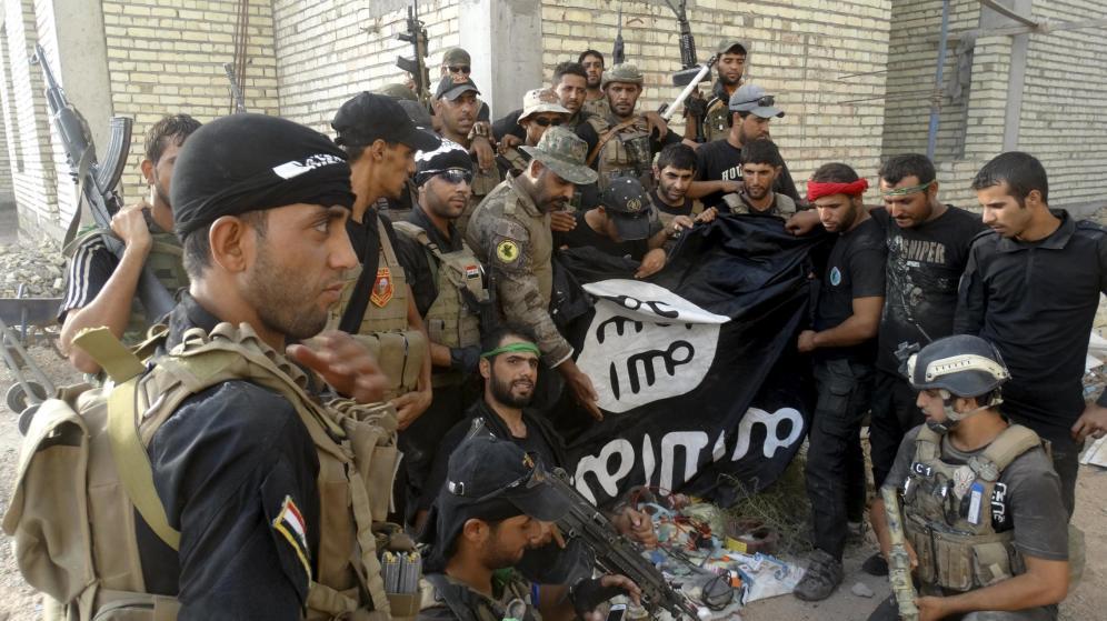 Miembros de las fuerzas de seguridad iraquíes sostienen una bandera del ISIS capturada en la Universidad de Anbar, en julio de 2015 | Vía: Reuters