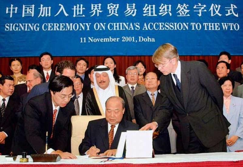 November 11, 2001, Shi Guangsheng, el entonces Ministro de Cooperación Económica y Asuntos Exteriores, firmando el protocolo de acceso a la Organización Mundial del Comercio | Vía: Qiushi Journal (Toward a more open China)